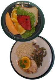 one plate holding a sandwich and fruit; another plate holding glazed chicken, green beans with mushrooms, and rice